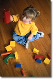 infant girl playing with blocks