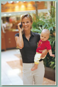 Mother carrying baby and talking on cell phone.